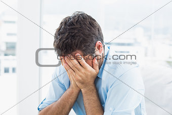 Man with head in hands sitting on the couch