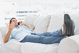 Smiling man lying on the couch talking on the phone