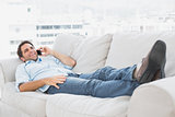 Happy man lying on the couch talking on the phone