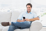 Cheerful man sitting on the couch using his smartphone