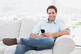 Happy man sitting on the couch using his smartphone