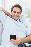 Smiling man sitting on the sofa texting on his phone