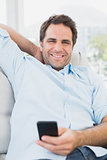 Smiling man sitting on the sofa texting on his phone looking at camera