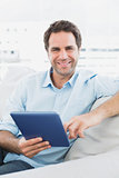 Handsome smiling man sitting on the sofa using his tablet pc