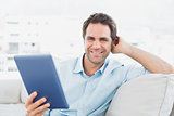 Handsome man sitting on the sofa using his tablet pc smiling at camera