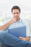 Thinking man sitting on the couch using his tablet
