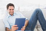 Smiling man relaxing on the couch using his tablet