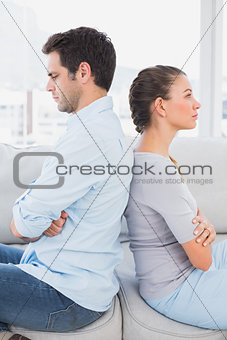 Annoyed couple sitting back to back on the couch