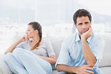 Man looking at camera with upset girlfriend on the couch