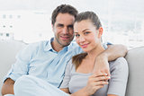 Couple sitting on the sofa smiling at camera