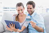 Happy couple relaxing on the couch shopping online with tablet pc