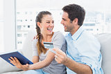 Laughing couple sitting on the couch shopping online with tablet pc