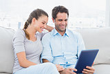 Smiling couple sitting on the couch using tablet pc