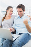 Excited couple sitting on the couch using laptop together