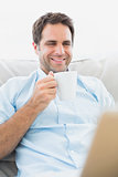 Smiling man using laptop sitting on sofa having a coffee