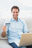 Smiling man using laptop sitting on sofa shopping online