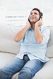 Happy man sitting on sofa listening to music