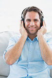 Happy man sitting on sofa listening to music smiling at camera