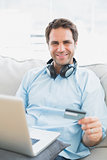 Smiling man sitting on sofa online shopping with laptop
