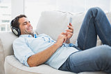 Happy handsome man lying on sofa using tablet and listening to music