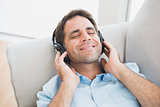 Smiling handsome man lying on sofa listening to music