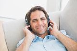 Smiling handsome man lying on sofa listening to music looking at camera