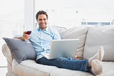Smiling handsome man relaxing on sofa with glass of red wine using laptop