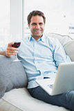 Handsome man relaxing on sofa with glass of red wine using laptop