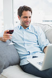 Happy man relaxing on sofa with glass of red wine using laptop