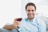 Happy man relaxing on sofa with glass of red wine