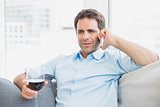 Cheerful man relaxing on sofa with glass of red wine talking on phone