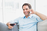 Happy man relaxing on sofa with glass of red wine talking on phone