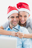 Happy couple in santa hats shopping online