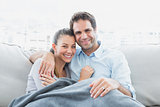 Cheerful couple relaxing on their sofa smiling at camera under blanket