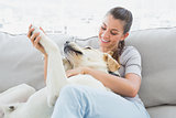 Happy woman petting her yellow labrador on the couch