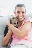 Pretty woman cuddling her yorkshire terrier on the couch