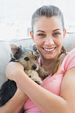 Smiling woman cuddling her yorkshire terrier on the couch