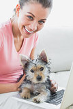 Cheerful woman using laptop with her yorkshire terrier