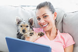 Attractive woman using tablet pc with her yorkshire terrier