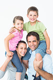Parents giving their children piggyback ride smiling at camera
