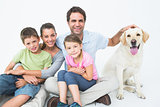 Cute family with pet labrador posing and smiling at camera together