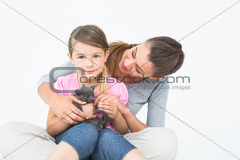 Happy daughter and mother sitting with pet kitten together