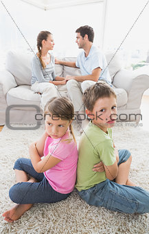 Pouting siblings sitting back to back while parents are arguing