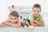 Siblings lying on rug with yorkshire terrier smiling at camera