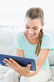 Happy woman sitting on couch using tablet pc