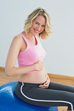 Smiling blonde pregnant woman touching belly on exercise ball
