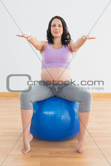 Pregnant woman sitting on blue exercise ball with arms outstretched