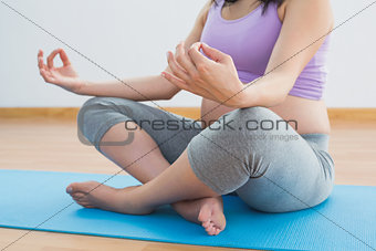 Pregnant woman sitting on blue mat in lotus pose