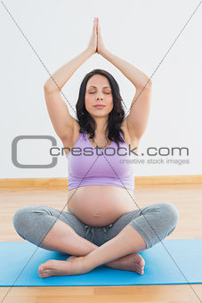 Pregnant brunette sitting on mat in lotus pose meditating