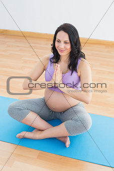 Pregnant brunette sitting on mat in lotus pose smiling
